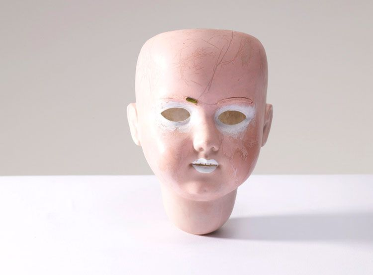 Kurt Cobain's Art. A porcelain doll head, redecorated with white and pink paint.