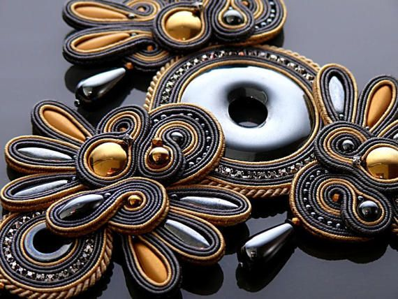 Beautiful, impressive soutache necklace, made of soutache strings with Hematite and glass beads.  Rear finished with natural leather.  Full length: 5.6 inches.  Length of string: 22.4 inches  Colour: beige gold and graphite.