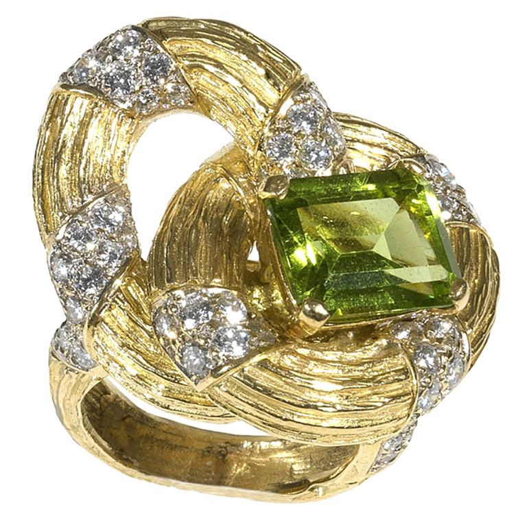 Peridot and Diamond Ring, BOUCHERON, Paris. Of ribbon form, with 64 round diamonds weighing approximately 3.84 carats, the center set with an emerald cut peridot weighing approximately 10.00 carats, ca. 1970s