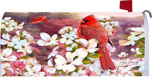 Cardinals mailbox cover featuring a close-up look at a beautiful red bird perched amongst an array of brilliant, white dogwood blossoms while a second cardinal is seen soaring off into the distance. T