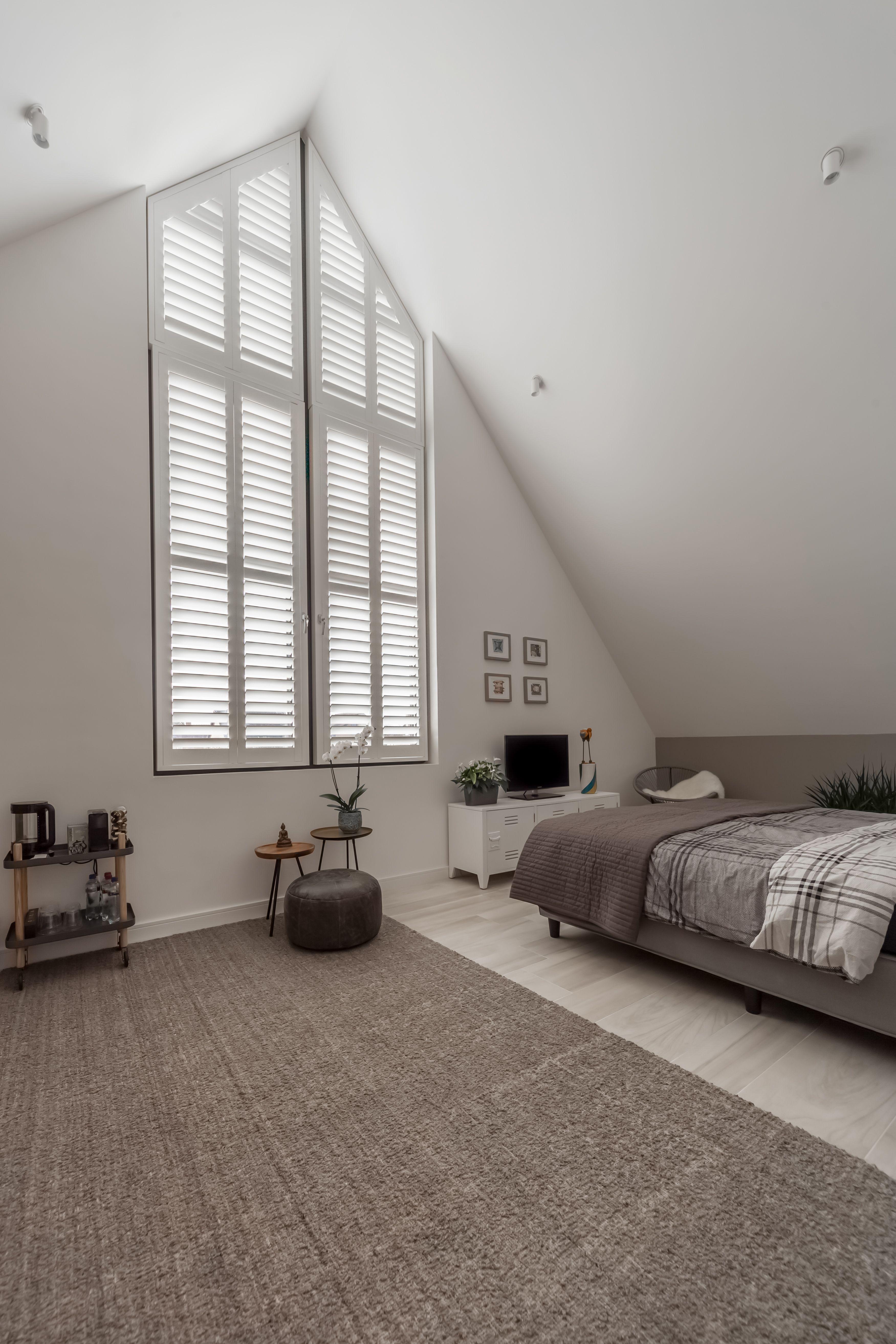 Schitterend hoog driehoekig raam met witte shutters in de slaapkamer ...