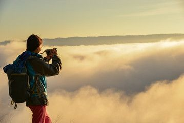 cheering woman at mountain peak,woman trekking among mountian on  mist sunrise,Tourist with backpack crossing mountian at sunrise ,Tourist useing camera on mist sunrise