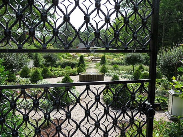A Beautiful Spanish Looking Wrought Iron Gate Leading To A Parterre With A  Contemporary Mill Wheel Fountain. Boxwood, Roses, Topiaried Flowering Trees  And ...