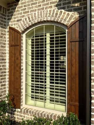 Outside View Of Arched Shutter On A Brick Wall Farmhouse