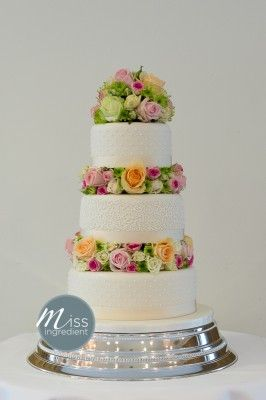 Wedding Cake With Roses And Flowers As Separators Between The Tiers