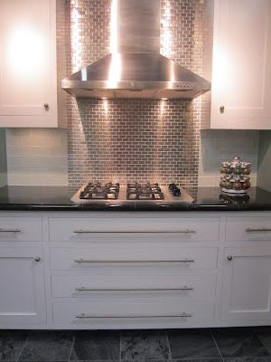 Stainless behind cooktop with natural stone around it For the