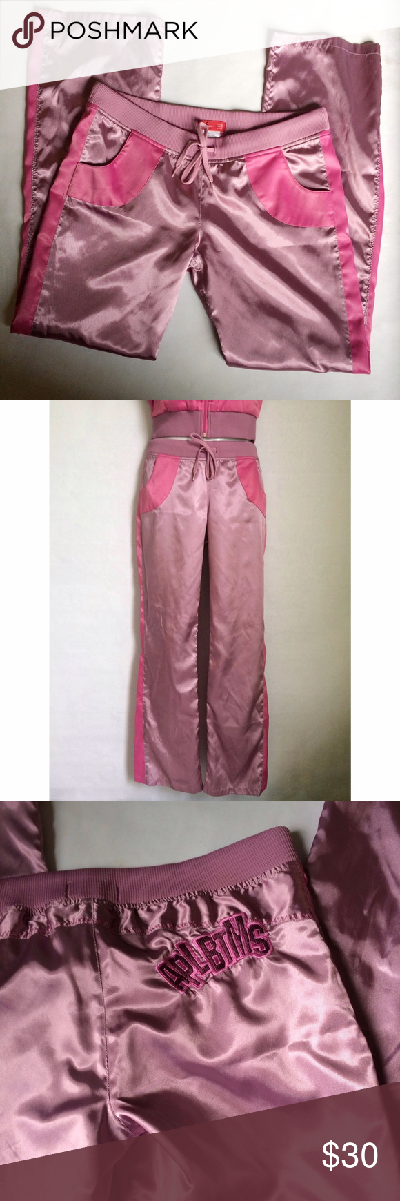 ✨NEW Listing✨Apple Bottoms satin pants Apple Bottoms satin track pants in lavender with pink trim on sides and curved trim on pockets. Drawstring waist with APLBTMS appliqué on back. Lined to thigh. Size L. 97% polyester/3% spandex. Matching jacket (size M) available in a separate listing. Not interested in trades. Apple Bottoms Pants Track Pants & Joggers
