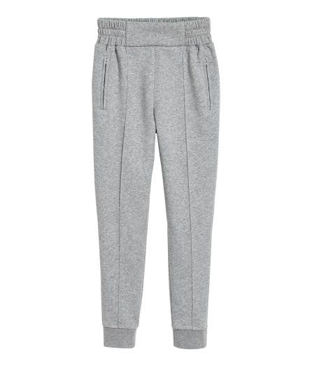 Joggers in melange sweatshirt fabric. Wide elastication at waist, side pockets with zip, and tapered legs with sewn creases and ribbed hems.