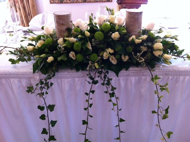Top table wedding flowers  - country style with bark wrapped candles and cream flowers. Ivy gathered from the countryside where the bride lives...