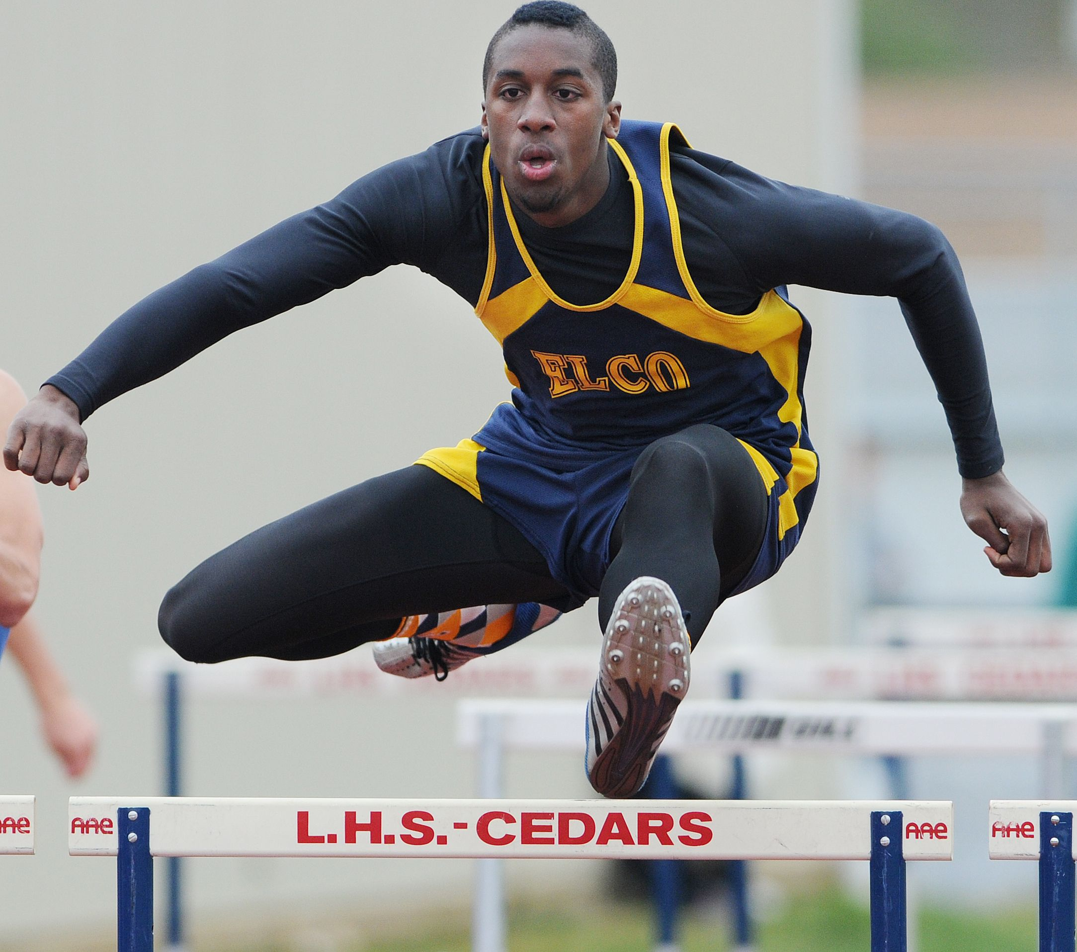 Elco's Nate Litschi soars over a hurdle on his way to a