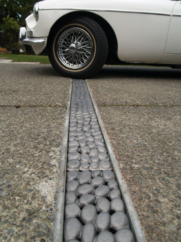 River rock trench grate by iron age designs landscape for Driveway trench drain