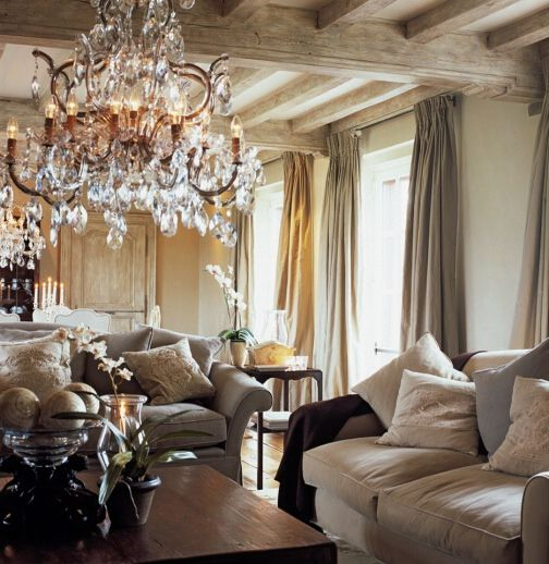 house of porters Beamed ceiling linen slip covers and drapery. Big chandilier in the center