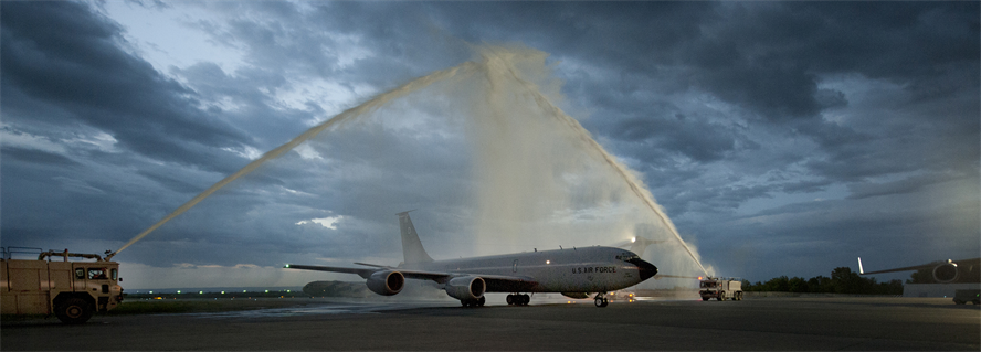 """Fire trucks spray water over a KC-135 Stratotanker during the final flight for Col. Corey Martin June 4, 2013, at theTransit Center at Manas, Kyrgyzstan. The """"fini-flight"""" is a time-honored military aviation tradition marking the last flight of a pilot's or commander's time with a unit. Martin is the 376th Air Expeditionary Wing commander. (U.S. Air Force photo/Staff Sgt. Robert Barnett)"""