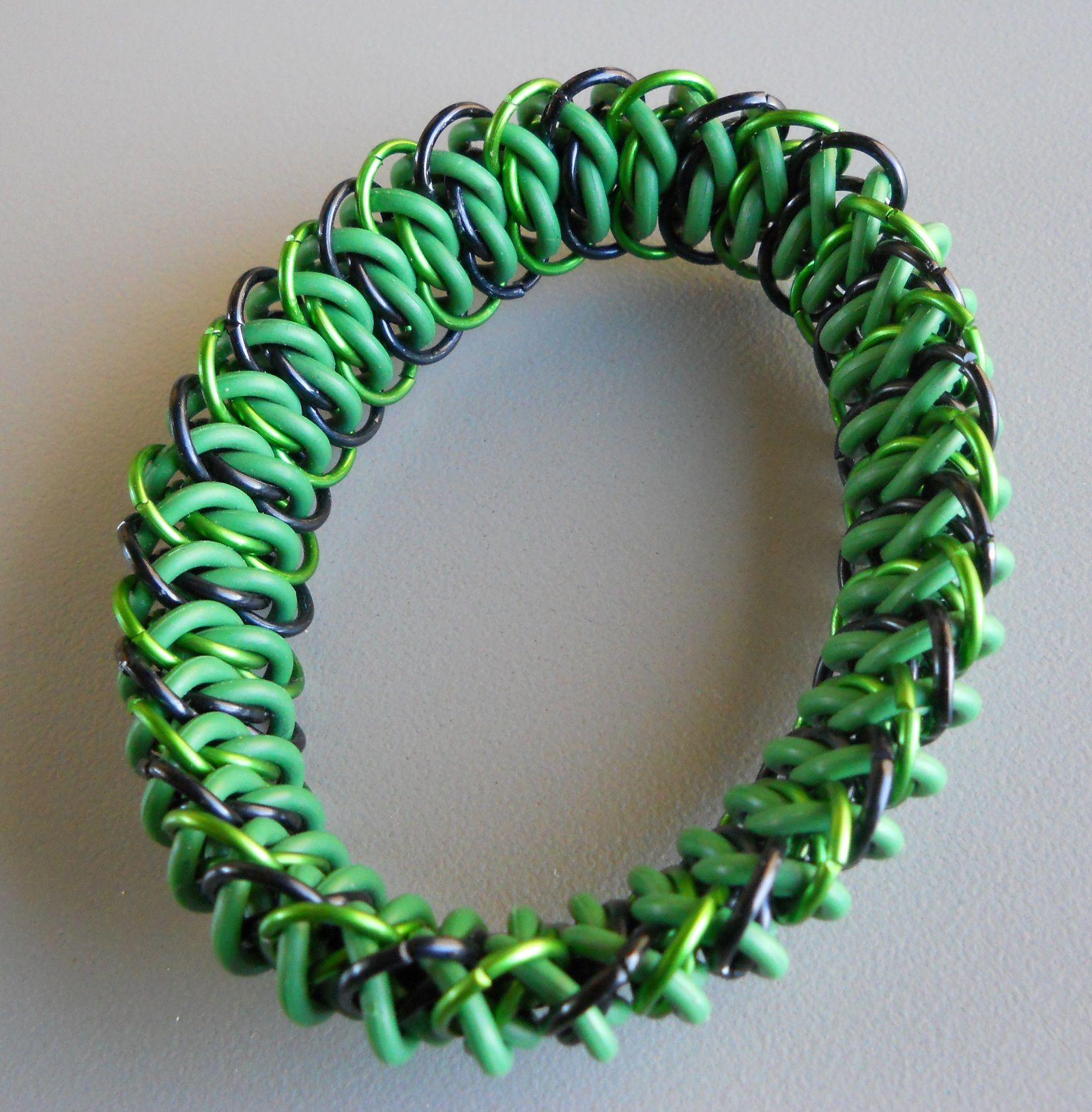 228. Green EPDM rubber rings with green and black anodized aluminum Viperscale pattern stretch bracelet. $25
