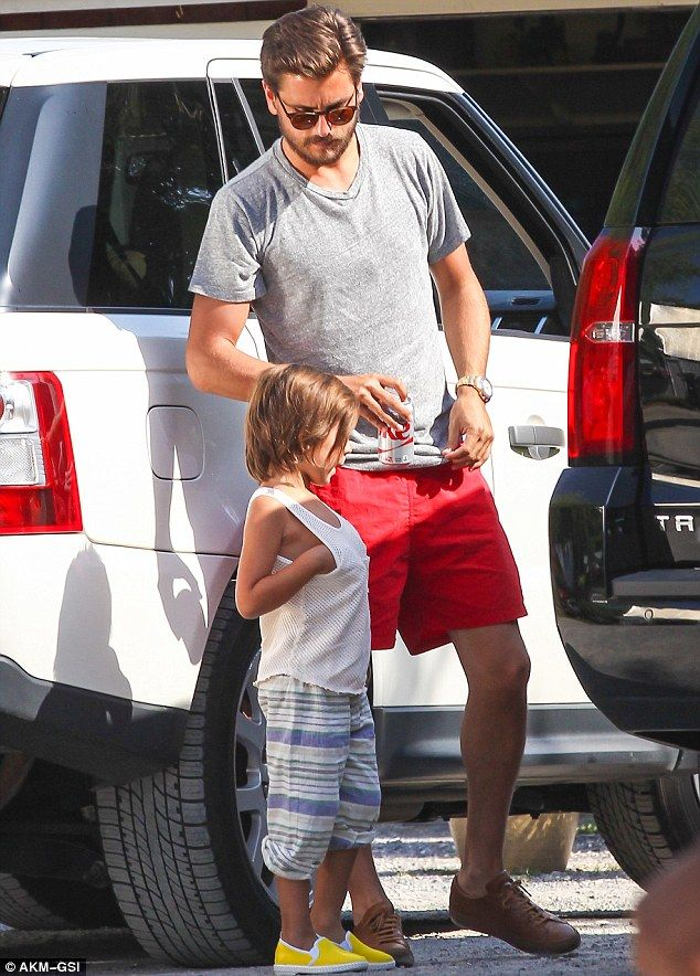 Father and son bonding: Scott sported bright red shorts and a grey ...