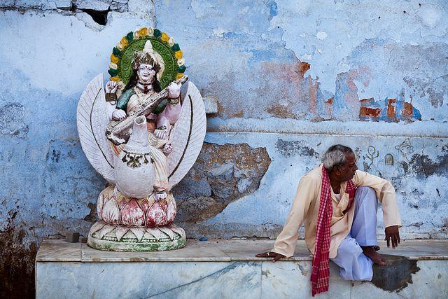 Man sitting on the ghats of Pushkar near a statue of hindu goddess Sarasvati, Rajasthan, India.