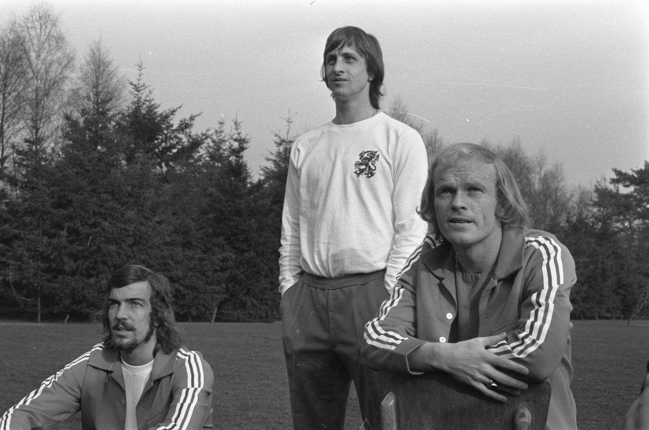 Nederlandse elftalselectie traint; debutant Ruud Geels (rechts) en Johan Cruyff kijken langs de kant toe (links Rene Notten )
