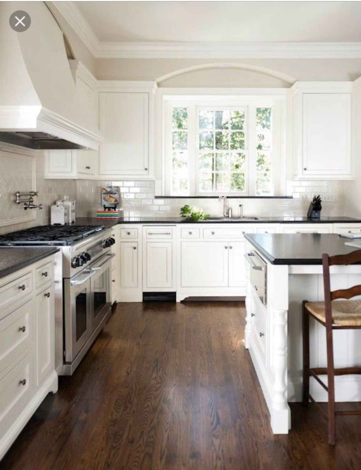 White kitchen wood floors and dark counters in