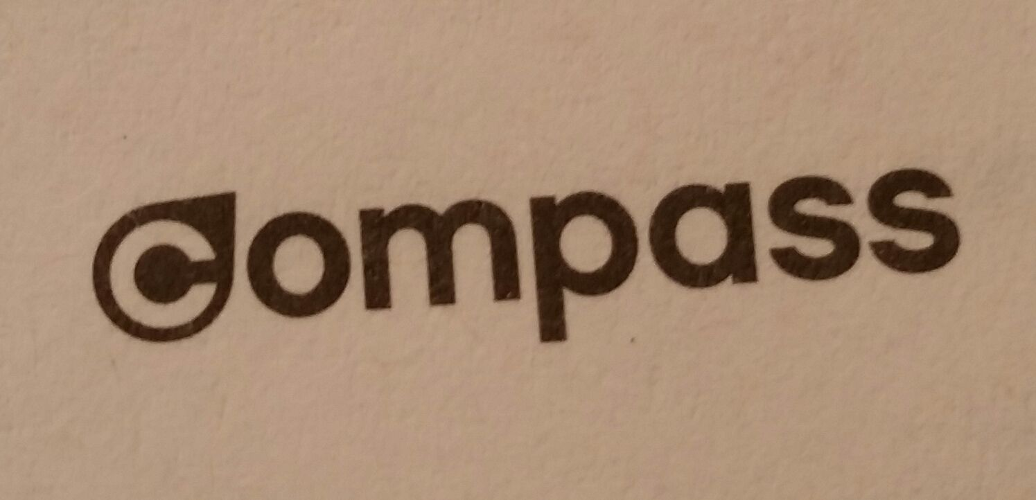 "The Compass logo is a wordmark with a stylized compass needle/indicator icon on the letter ""c."" The ""c"" is also reversed onto the black icon, creating a focal point for the logo. With a sans-serif typeface and all lower-case letters, the logo has a modern and clean look. Its simplicity and smooth appearance makes it a very versatile logo, allowing it to be placed on a variety of applications."
