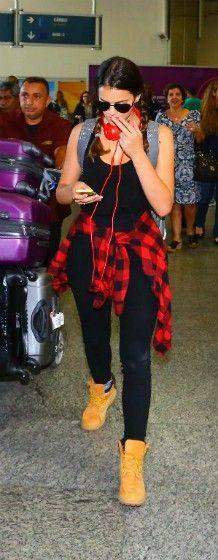 Bruna Marquezine foi vista em um aeroporto com um look bem confortável e estiloso . Para deixar a combinação de calça preta cintura alta e regata preta , ela usou uma camisa xadrez amarrada na cintura e botas timberland