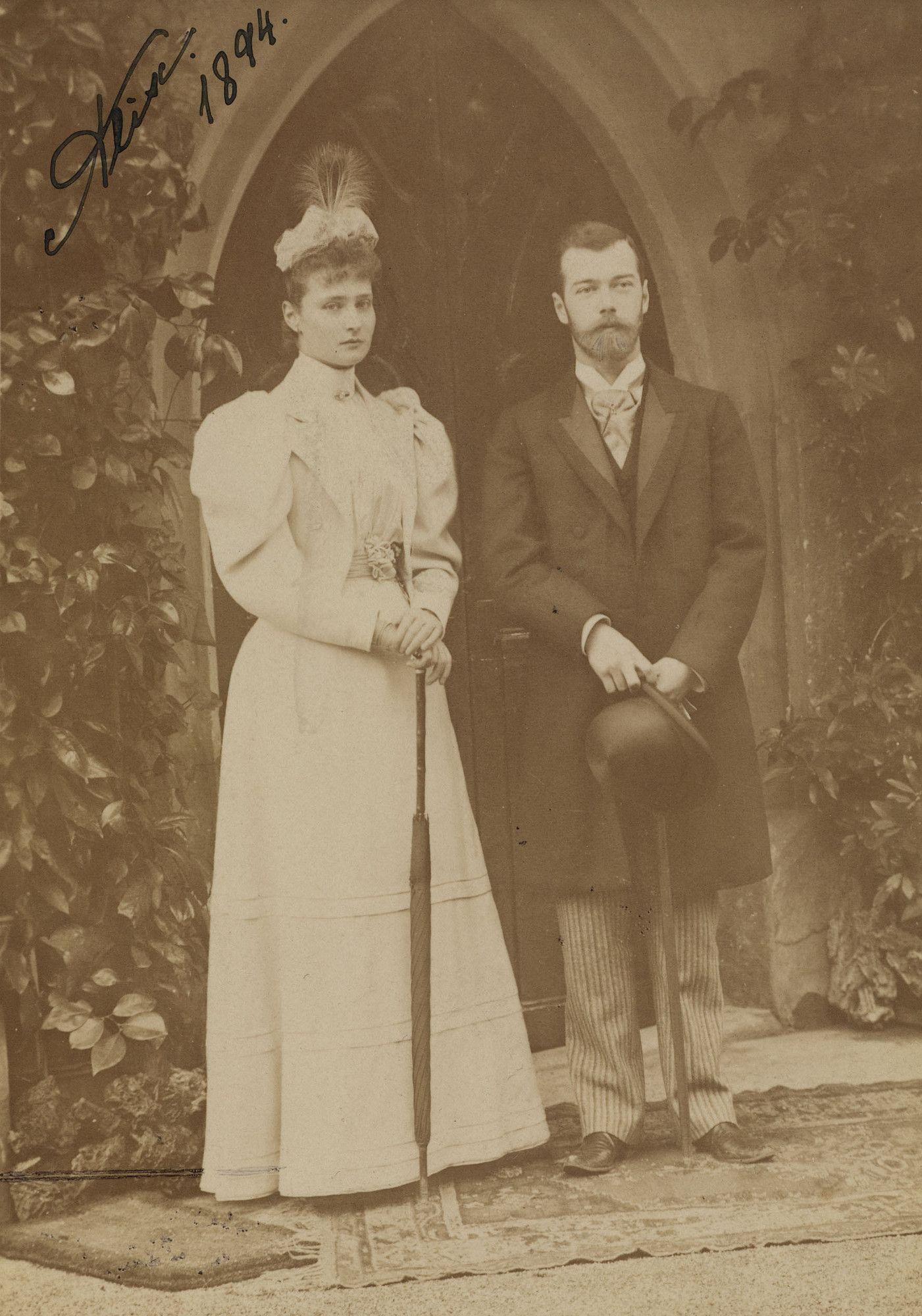 Tsarevich Nicholas está de pé à direita, segurando um chapéu e uma bengala. Princesa Alix está de pé ao lado dele, à esquerda segurando um guarda-chuva dobrado e usando um chapéu decorado com uma pena. Eles estão de pé sobre um tapete modelado e há uma porta gótica por trás deles. Esta fotografia foi tirada em Coburgo, em abril 1894, no momento do seu noivado, que ocorreu durante as celebrações do casamento de sua prima mútua Princesa Victoria Melita.
