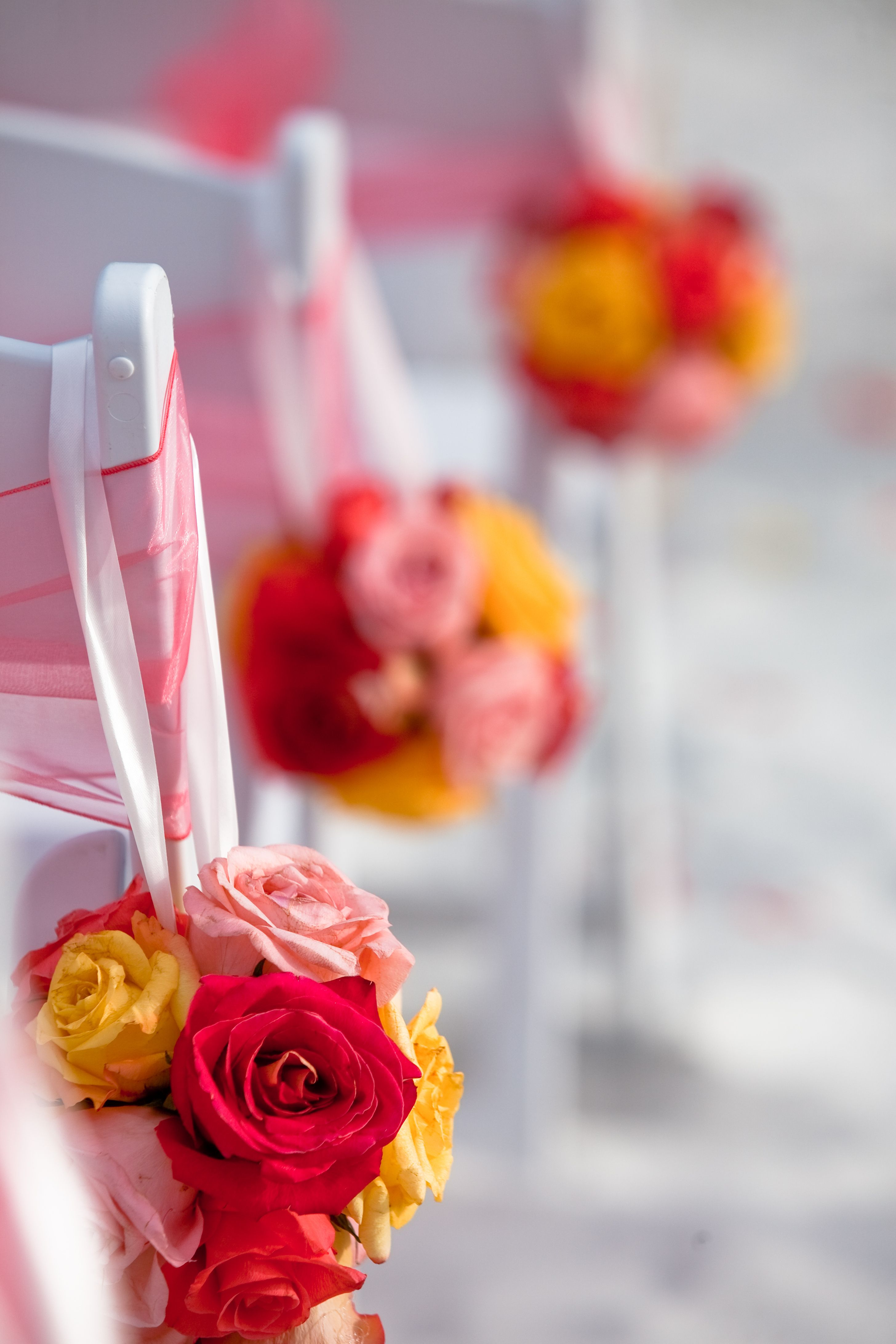 Coral And Yellow Flower Balls Hung On White Wooden Folding Chairs