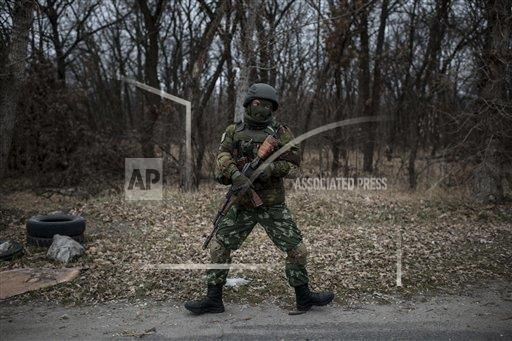 A Ukrainian serviceman shows off his dance moves to warm himself while manning a position next to a bridge over the river Siverskiy Donets damaged by explosions during a fighting between Pro-Russian rebels and Ukrainian government forces near Trehizbenka village, Luhansk region eastern Ukraine, Sunday, November. 23, 2014.More than 4,300 people have died in fighting in eastern Ukraine over the past half year, according to U.N. estimates. (AP Photo/Evgeniy Maloletka)