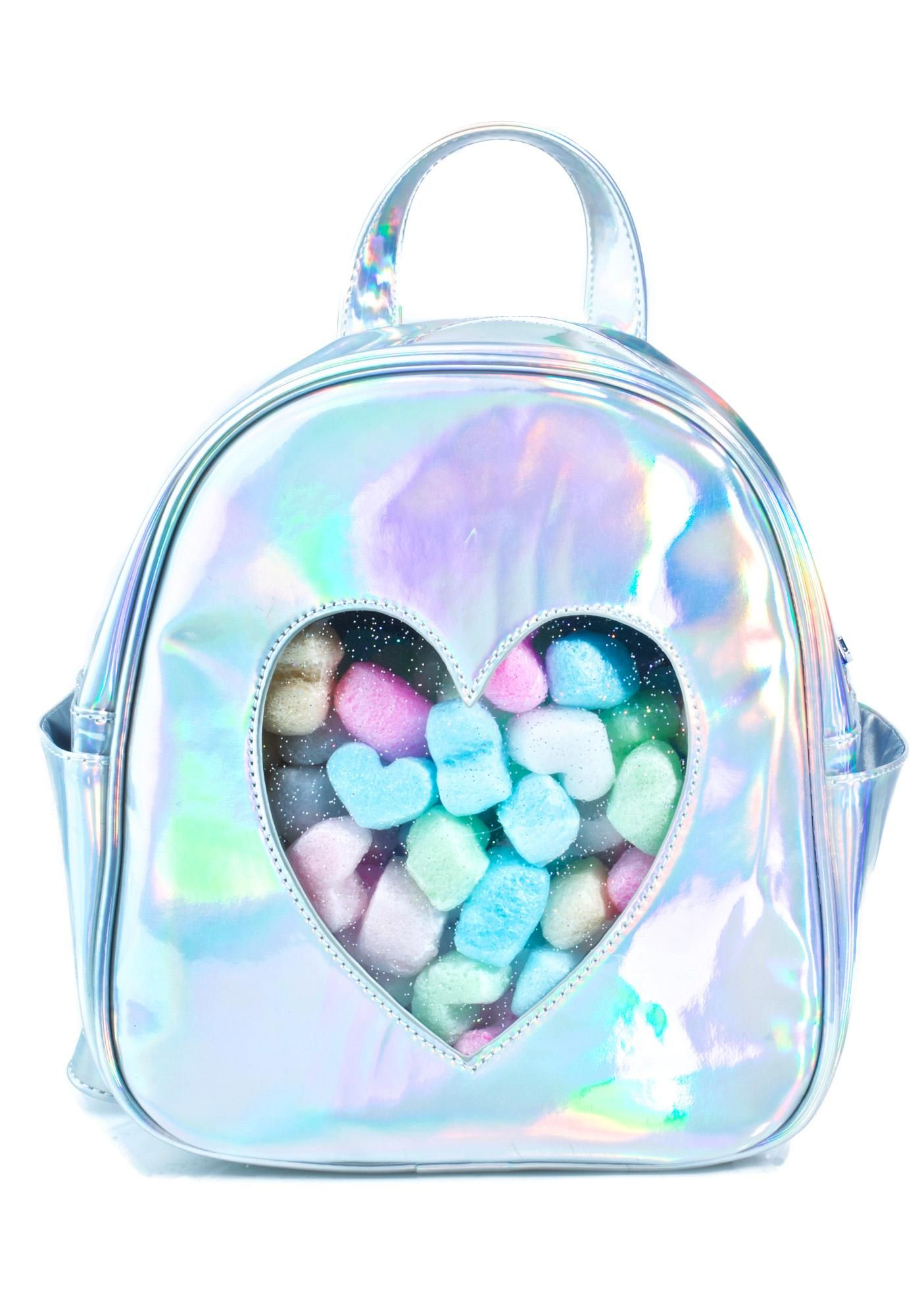 Sugarbaby Sweetheart Backpack what's in yer bag, kitten?! Give 'em a sneak peek into yer life with this adorable backpack, featurin' a hyper holographic silver construction, top zip closure, side pockets, a transparent heart cutout across the front, and adjustable straps.