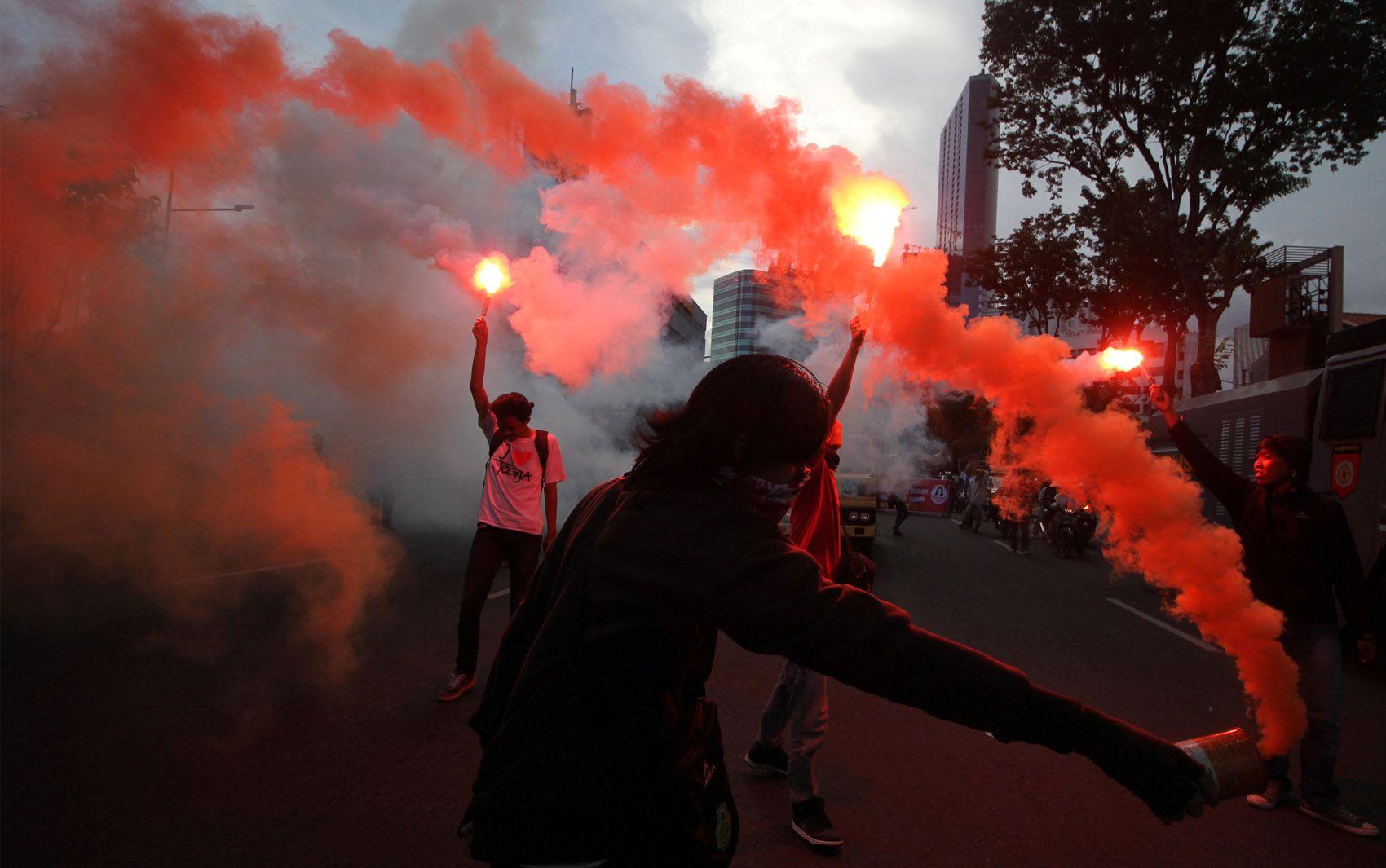 Trabalhadores utilizam sinalizadores durante um protesto do dia do trabalho em Surabaya, na Indonésia, nesta segunda (2)