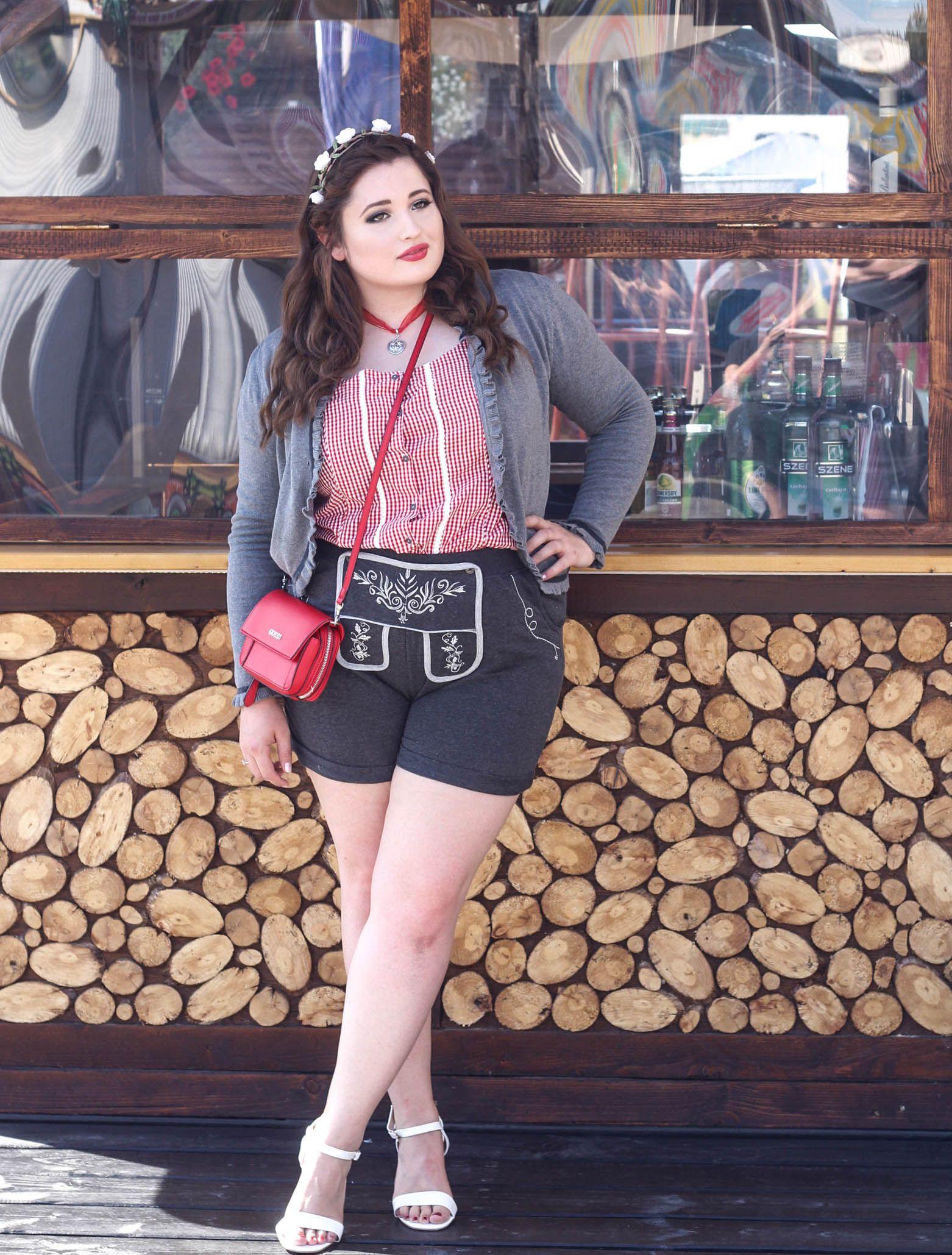 2df9d7fa0c4afc Junge kurvige Frau vor einer Holzhütte im Oktoberfest Outfit. Plus Size  Lederhosen Look.