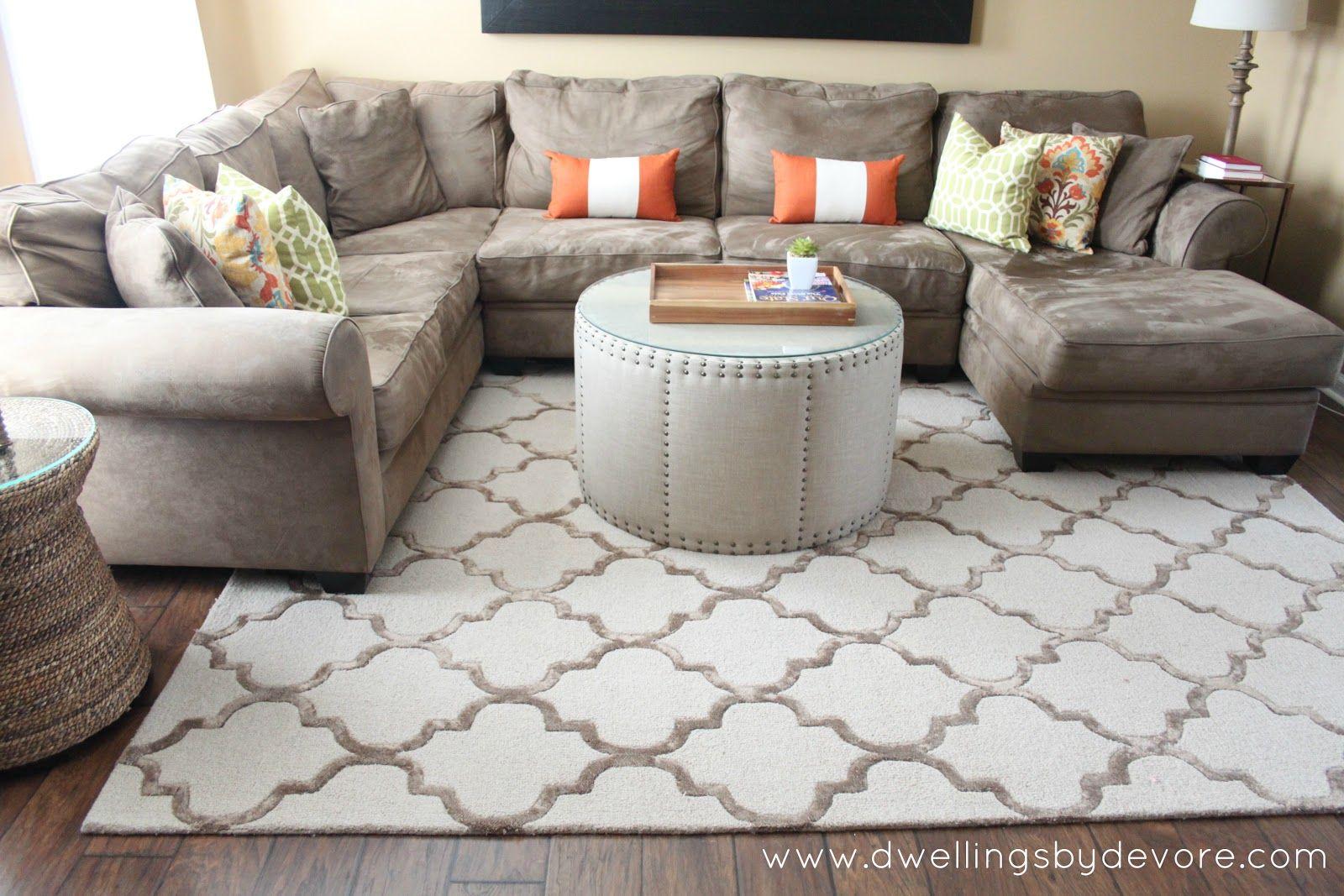Coloured throw cushion on taupe sofa round ottoman