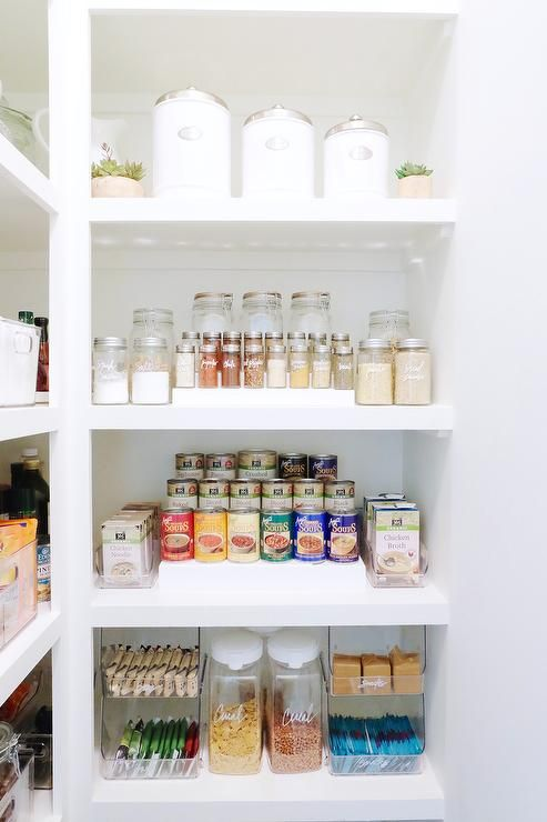 Bright, white pantry boasts top row lined with white labeled ...