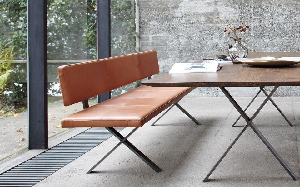 Die Bank zum Tisch gibt es in drei Ausführungen: mit hölzerner Sitzfläche, in Naturleder oder mit Stoff bezogen.