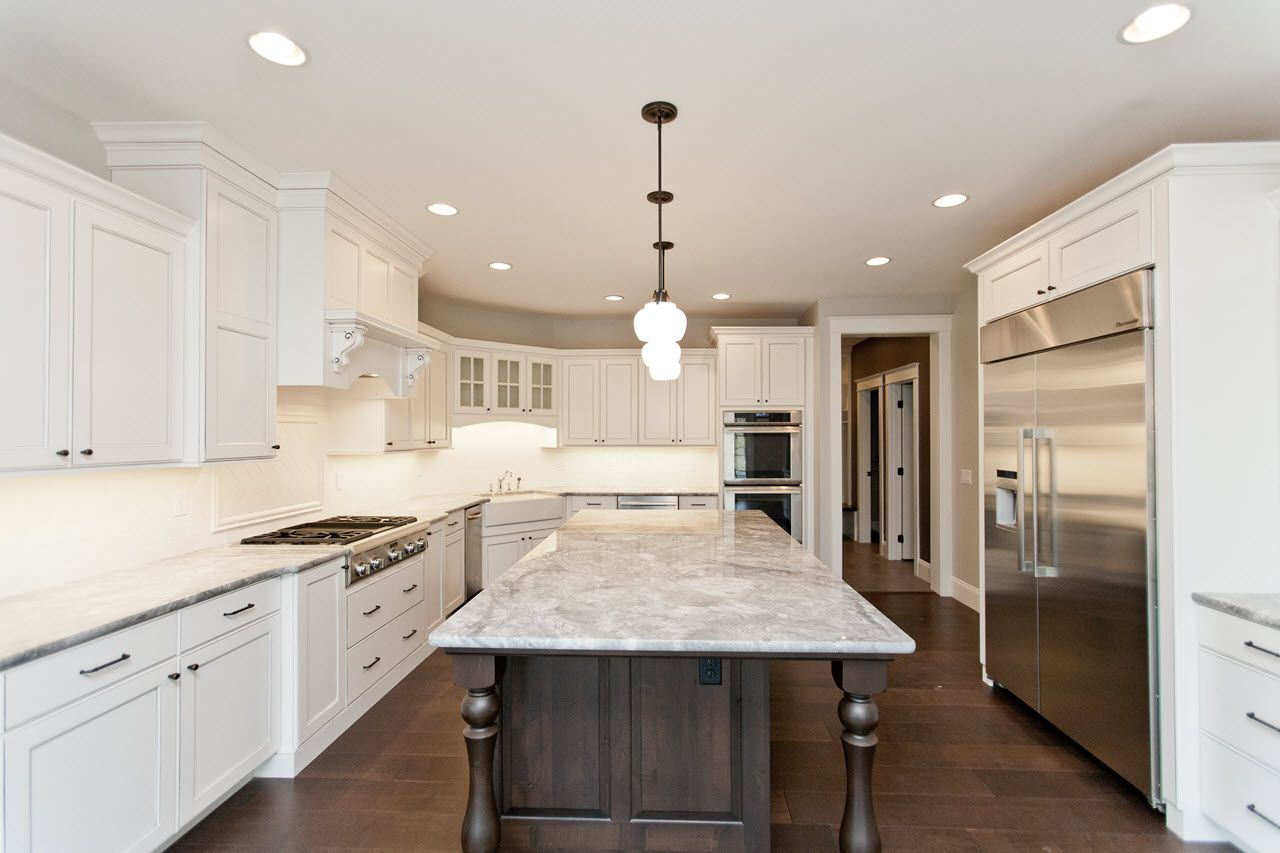 Stunning White Kitchen Cabinets With Large Island In Wood Tone Skogman Homes Cedar Rapids Iowa Whitekitch Kitchen Kitchen Inspirations White Kitchen Cabinets