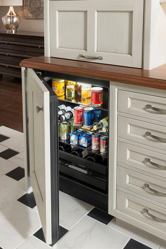 An undercounter mini-fridge surrounded by stylish Wood-Mode ...