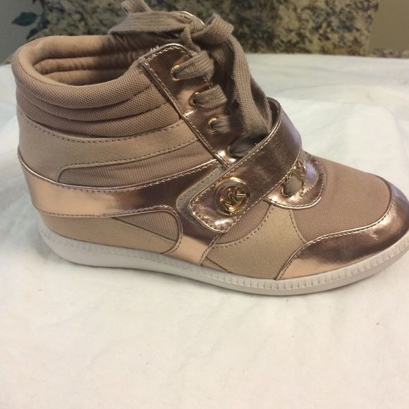 Michael Kors Rosegold high top sneakers Is there authentic preowned Michael KorsRosegold nylon and leather high top sneakers.  They are in good preowned condition with normal signs of wear. Still have a lot of great use. And lace and Velcro closure with MK signature emblem.  White rubber sole.  Please let me know if you have any questions Michael Kors Shoes Sneakers