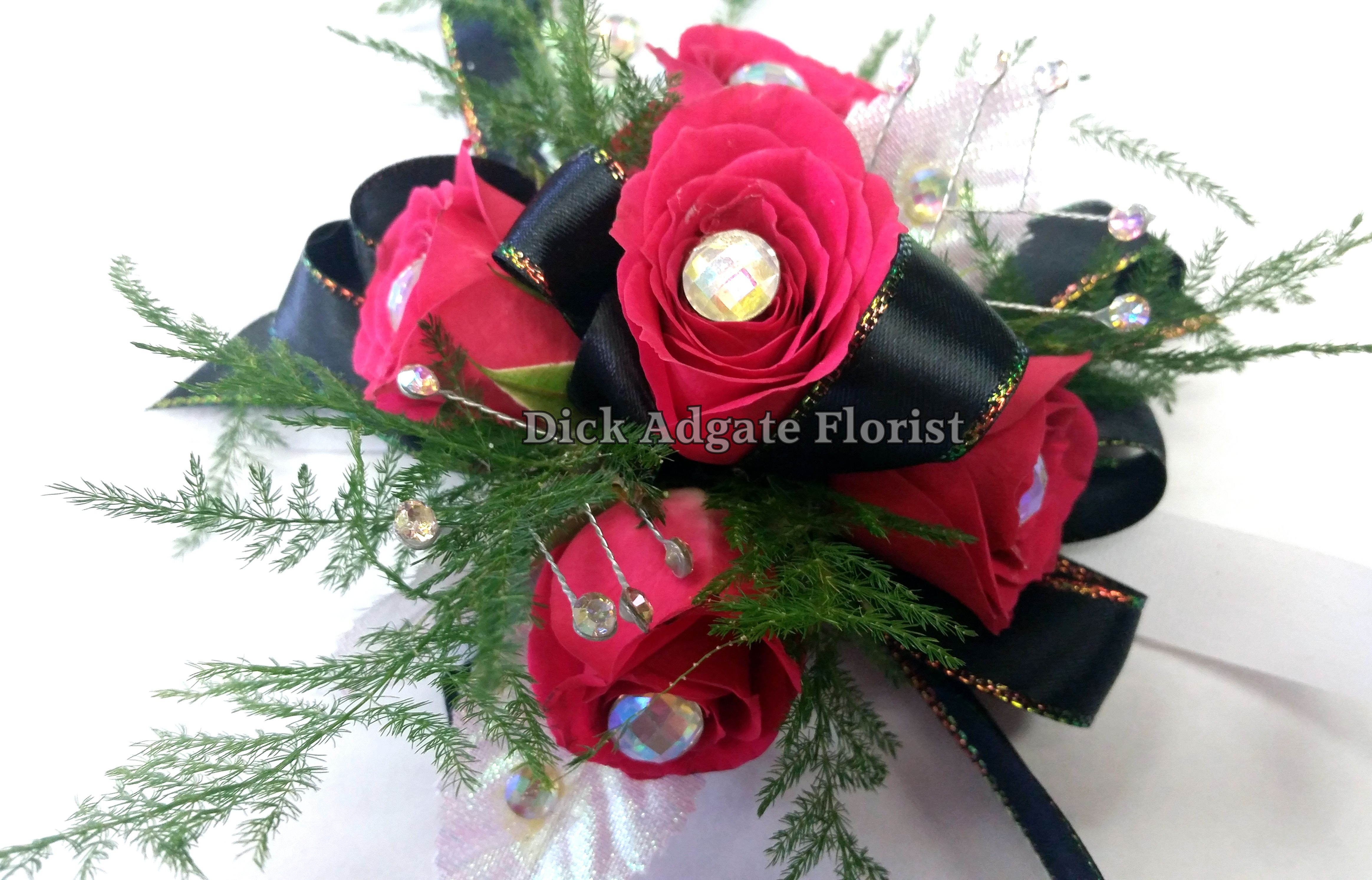 Hot pink spray roses with an iridescent gem in each, plumosa filler and a black ribbon lined with iridescent. Prom / homecoming flowers on a wrist corsage. Dick Adgate Florist original.