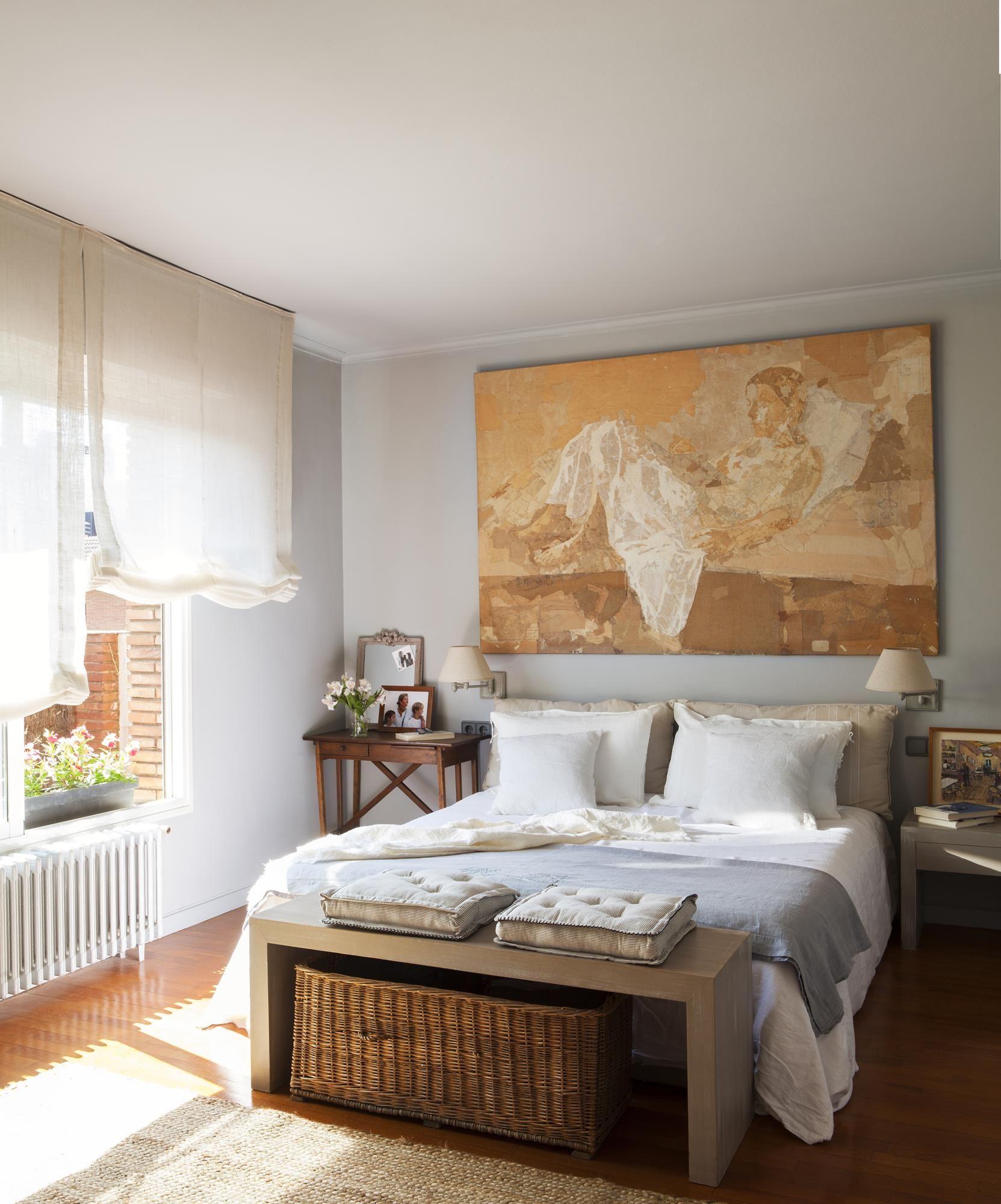 dormitorio con cesto y banco a los pies de la cama