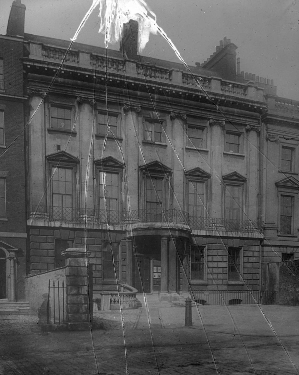 Unknown building, London c1900. Curious ghost-like figure at a gate. Probably the result of a long exposure by the photographer.