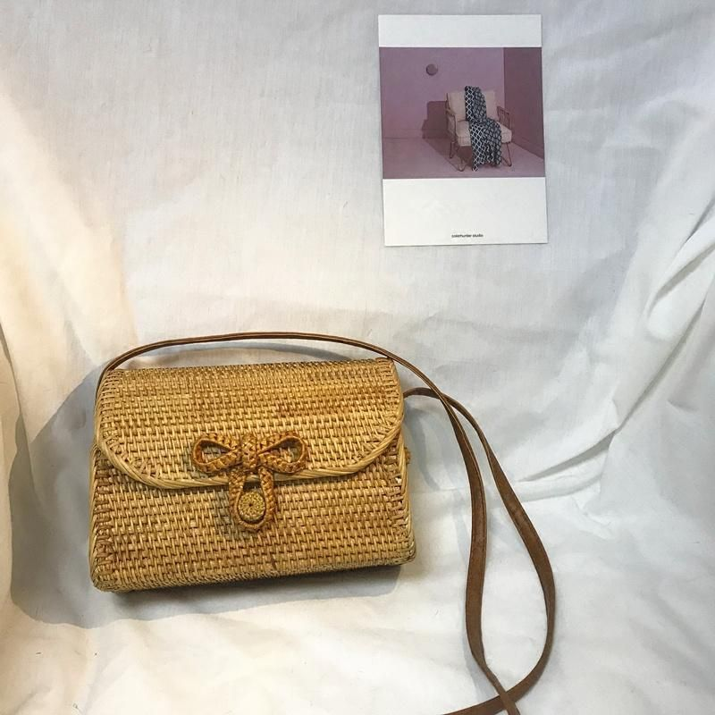 """Are you on the hunt for an """"IG-worty"""" beach bag? Look no further than this exquisite rattan satchel! This handmade rattan shoulder bag has a durable woven rattan body and features a cute bow accent that adds visual interest to its minimalistic design. This bag's cuteness will make you and other people around you smile under the sun! ✓ Easy and comfortable to carry✓ Hasp closure with an adorable bow accent✓ Best for carrying small items like keys, chapstick or cash✓ Extra long PU leather strap✓ C"""