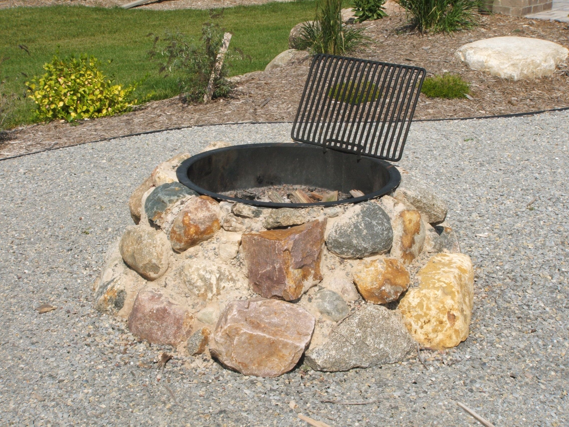 field stone firepit fire pit using granite boulders built into