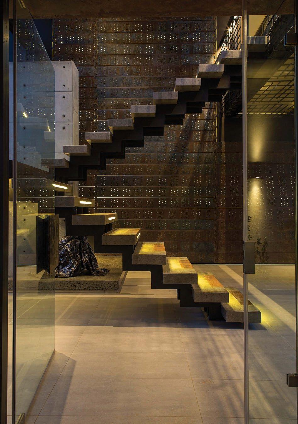 escaleras con cualidades escultricas con una piel perforada de metal oxidado y un muro de concreto