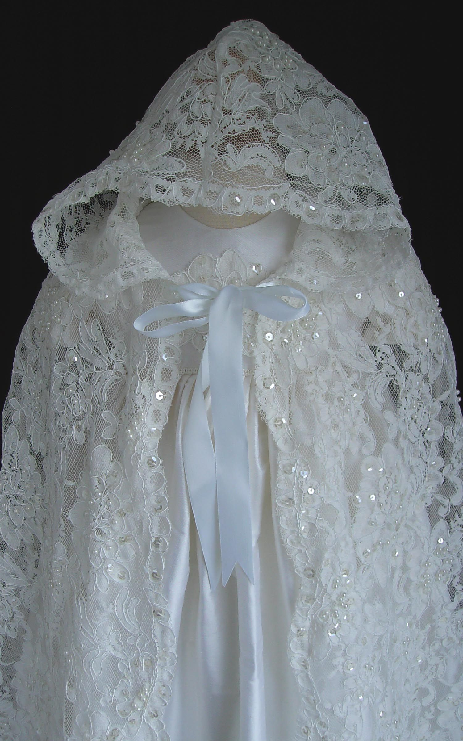 An elegant white dupioni silk christening gown of royal length with