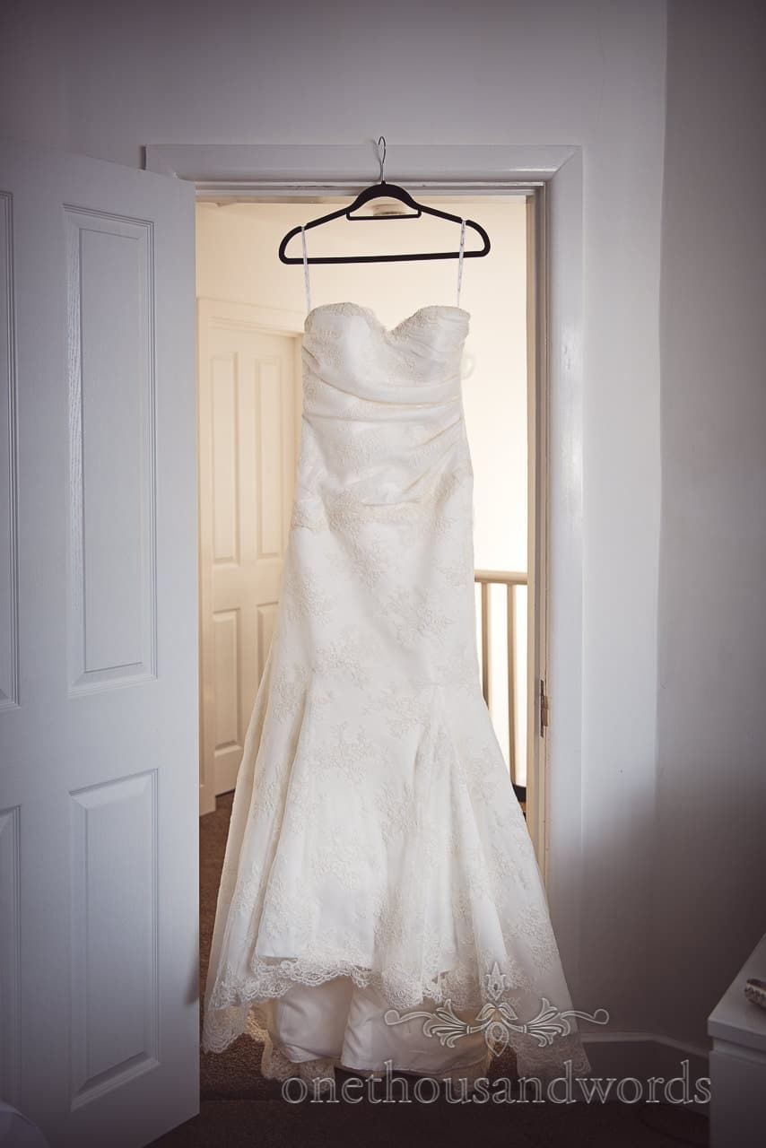 White trumpet skirt strapless wedding dress with lace detail hangs ...