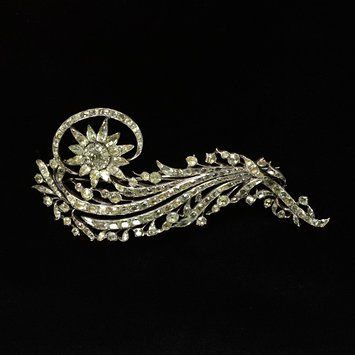 An Aigrette, courtesy of the Victoria & Albert Museum: Aigrette of chrysoberyls set in silver, in the form of a spray with a single flower; feathered scrolling stem. Place of Origin - Portugal  Date - ca. 1750-1760