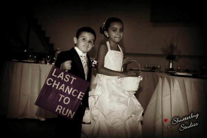 """Flower girl and ring bearer with sign that says """" Last chance to run"""""""