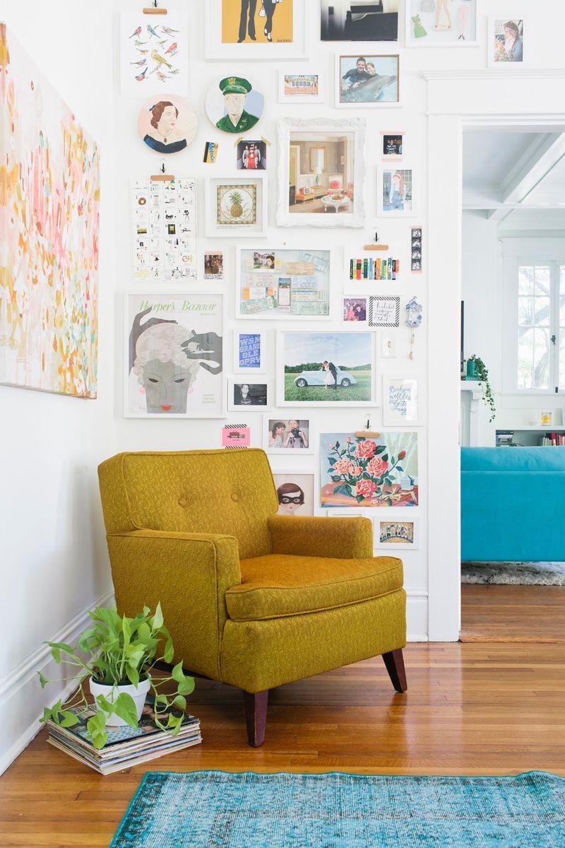Bellissima questa parete piena di quadri, stampe e fotografie! Tutto in perfetta armonia con la poltrona color ocra e il tappeto turchese.