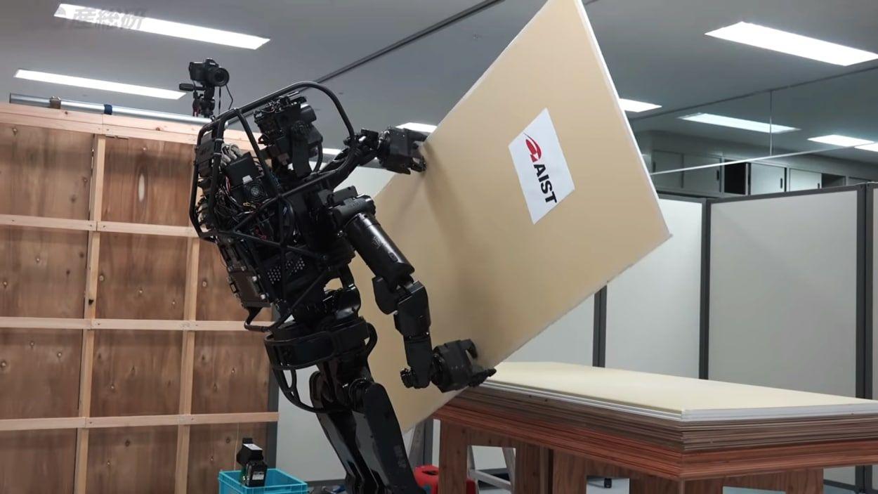 robot HRP5P en train de saisir une plaque de plâtre sur