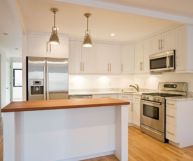 small efficient kitchen design with white shaker kitchen cabinets with white carrara marble countertops white kitchen island with butcher block countertop