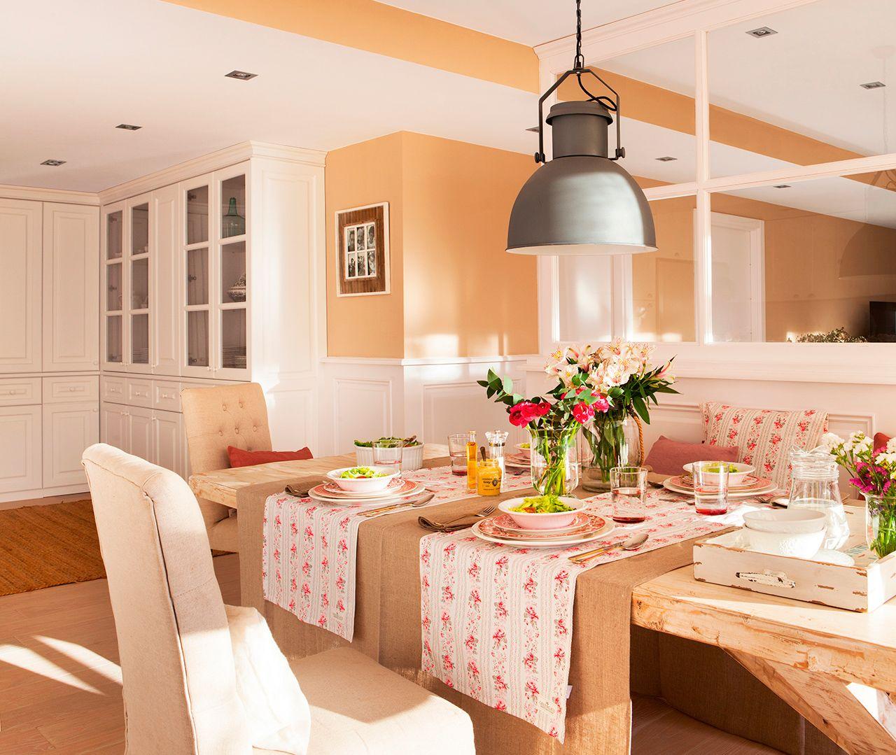 Comedor con mesa de madera, mantelería de flores y vista de armarios ...